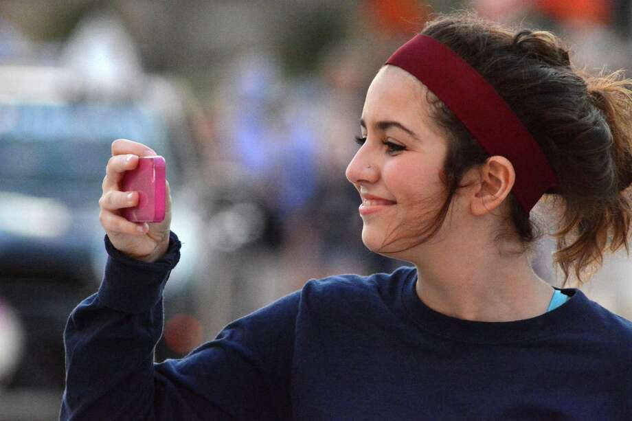 "Karina Pena, 15, a Tomball Memorial High School sophomore, is all smiles as she photographs her friends during the school's First Annual ""Rock the Block"" Homecoming Parade. Photo: Jerry Baker, Freelance"