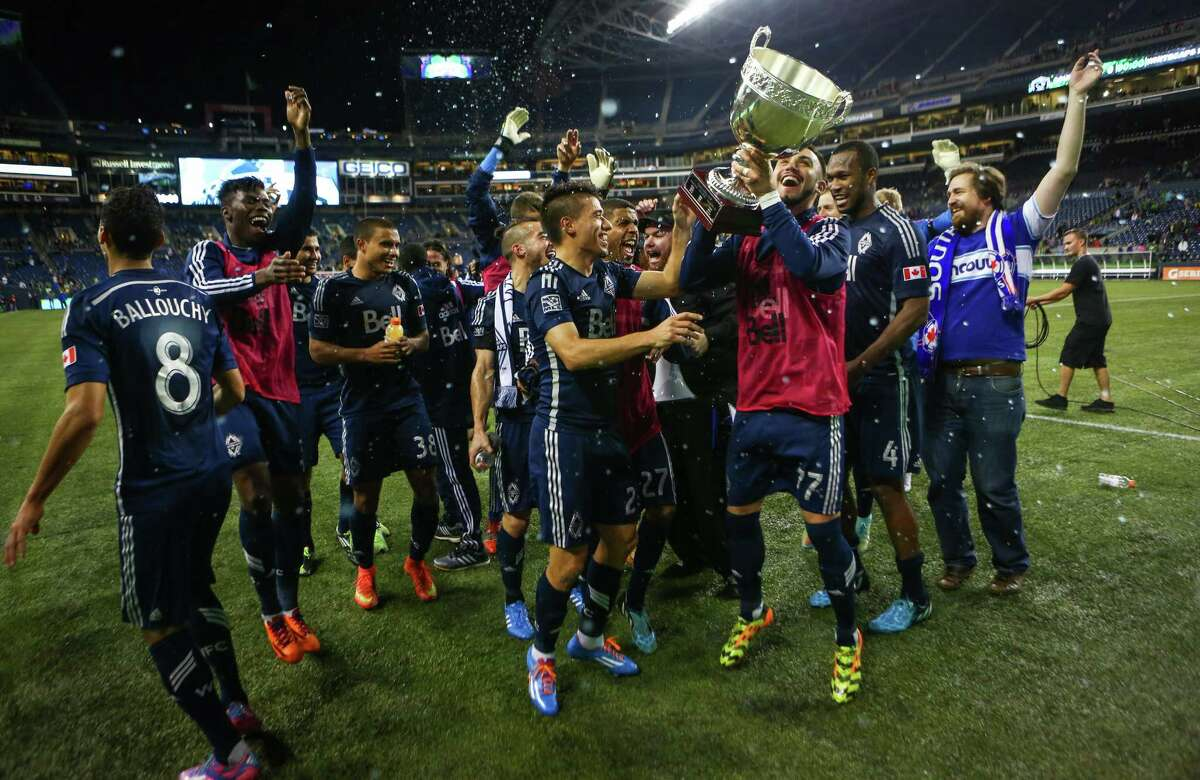 Vancouver Whitecaps players celebrate after defeating the Seattle Sounders on Friday, October 10, 2014. The Whitecaps won the Cascadia Cup after beating the Sounders 1-0.