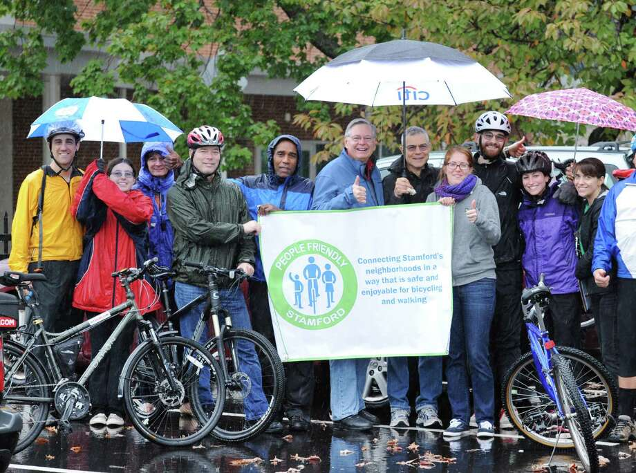 Stamford Mayor David Martin, center, with thumb held up, helps to hold a People Friendly Stamford banner with others during the Mill River Greenway Ride & Rally for the expansion of the Mill River Park Greenway and new bike lanes in Stamford, at  Scalzi Park, Stamford, Conn., Saturday morning, Oct. 11, 2014. Photo: Bob Luckey / Greenwich Time