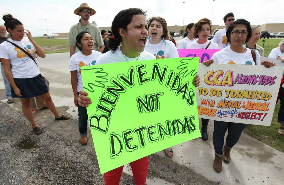 Andrea Ortiz of Austin (center) joins others in a chant for justice for immigrants at the Karnes County Residential Center near Karnes City on Saturday, Oct. 11, 2014. About 100 protesters gathered to demand the closing of the facility and for the release of immigrants detained at the facility. Photo: Kin Man Hui, San Antonio Express-News / ©2014 San Antonio Express-News