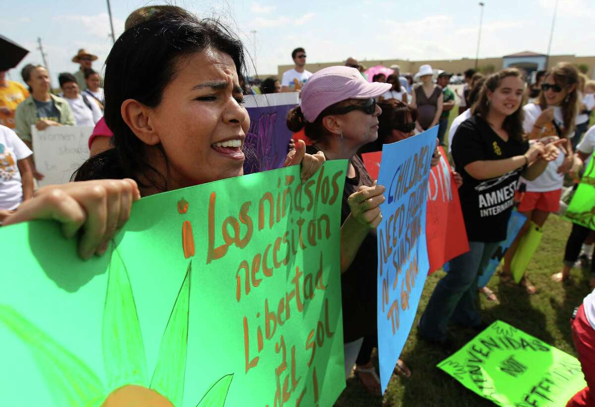 """Ariel Arriaga (left) carries a sign in Spanish that reads: """"children need freedom and the sun to grow"""" during a rally in front of the Karnes County Residential Center near Karnes City on Saturday, Oct. 11, 2014. About 100 protestors rallied to demand the closing of the facility and for the release of immigrants detained at the center."""