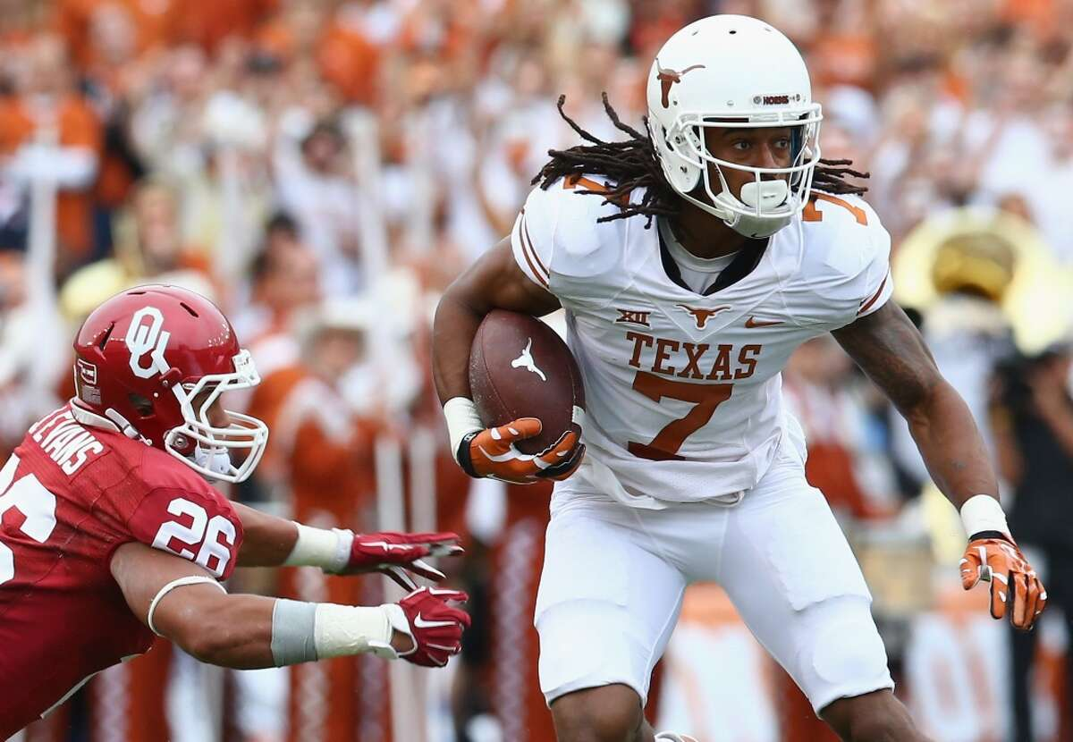 DALLAS, TX - OCTOBER 11: Marcus Johnson #7 of the Texas Longhorns runs the ball against Jordan Evans #26 of the Oklahoma Sooners at Cotton Bowl on October 11, 2014 in Dallas, Texas. (Photo by Ronald Martinez/Getty Images)