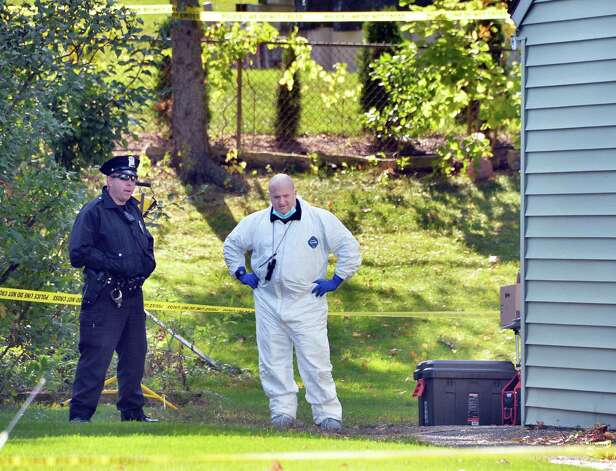 A police officer and an investigator in the backyard of 1846 Western Ave. Saturday Oct. 11, 2014, scene of a quadruple murder earlier this week in Guilderland, NY.  (John Carl D'Annibale / Times Union) Photo: John Carl D'Annibale / 10029010A
