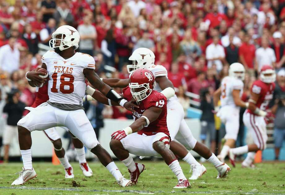 DALLAS, TX - OCTOBER 11:  Tyrone Swoopes #18 of the Texas Longhorns runs the ball against Eric Striker #19 of the Oklahoma Sooners at Cotton Bowl on October 11, 2014 in Dallas, Texas. Photo: Ronald Martinez, Getty Images / 2014 Getty Images
