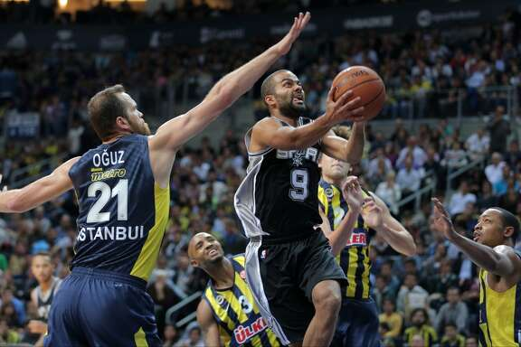 San Antonio Spurs' Tony Parker from France, center, tries to score during an NBA Global Games basketball match between US team San Antonio Spurs and Turkey's Fenerbahce Ulker, in Istanbul, Turkey, Saturday, Oct. 11, 2014. (AP Photo)