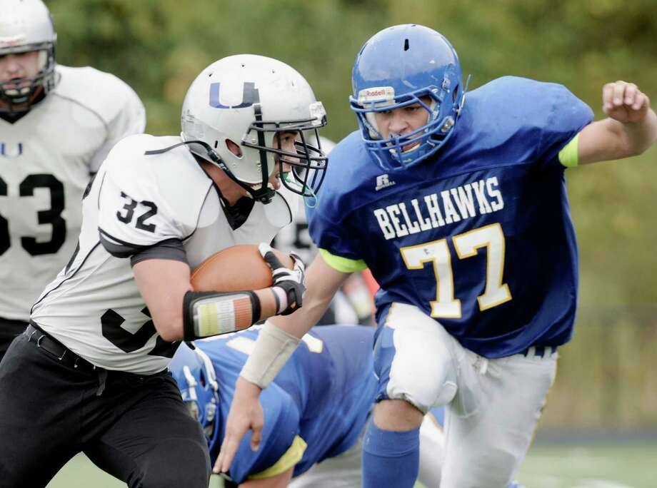 United's Angel Hernandez (32) tries to run around the Bellhawks Amos Talbott (77) during the football game between the Vinal Tech/East Hampton/Goodwin Tech Bellhawks and the Abbott Tech/Immaculate United, on Saturday, October 11, 2014, at Immaculate High School, in Danbury, Conn. Photo: H John Voorhees III / The News-Times Staff Photographer