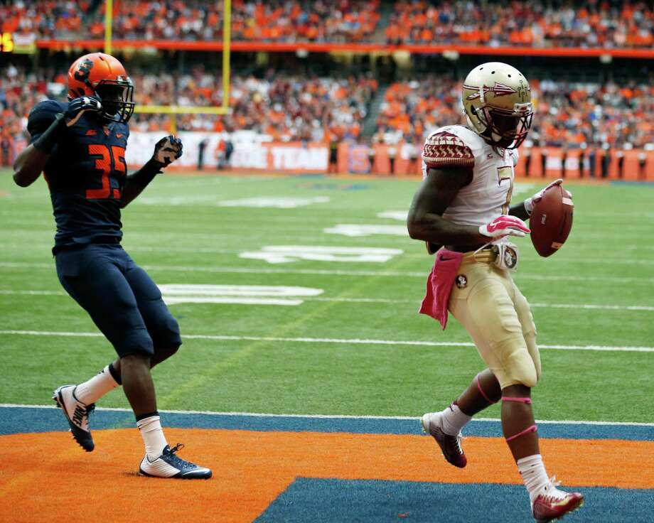 Florida State running back Mario Pender (7) scores on a touchdown reception in front of Syracuse linebacker Dyshawn Davis (35) during the first half of an NCAA college football game on Saturday, Oct. 11, 2014, in Syracuse, N.Y. (AP Photo/Mike Groll) ORG XMIT: NYMG104 Photo: Mike Groll / AP