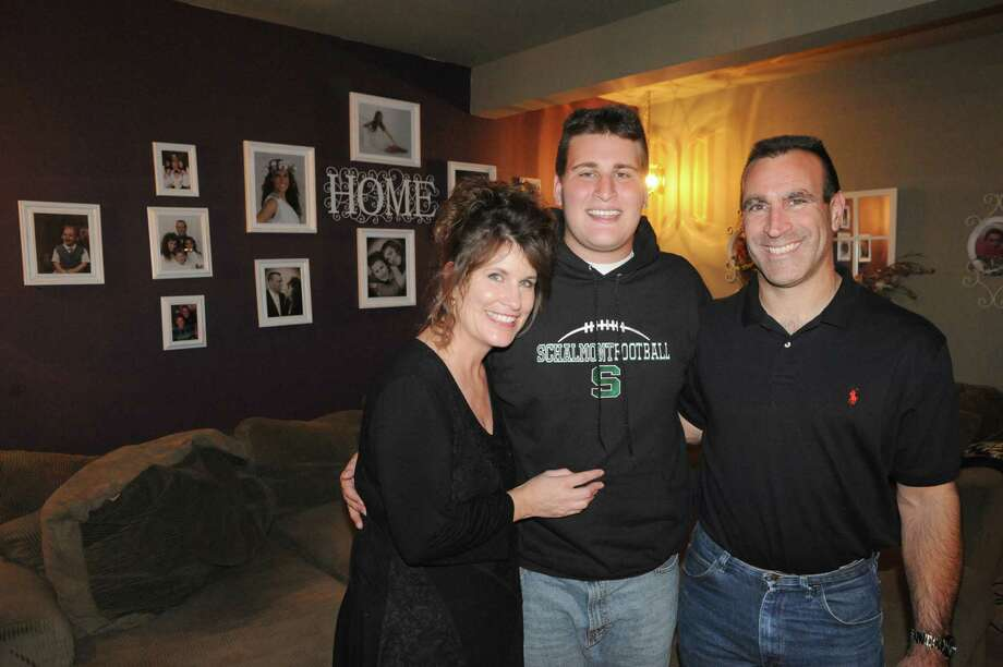 Dante Gallucci, center, a football player at Schalmont High School and cancer survivor, with his father Glenn Gallucci and mother Teri Gallucci on Thursday Oct. 9, 2014 in Rotterdam, N.Y.  (Michael P. Farrell/Times Union) Photo: Michael P. Farrell / 10028945A