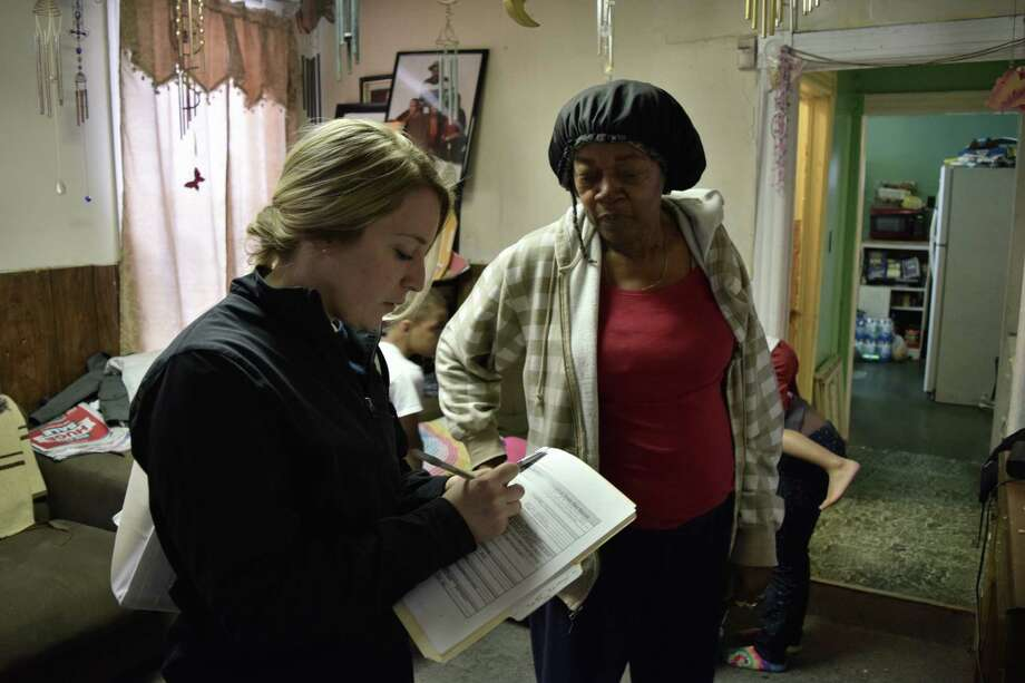 A Schenectady firefighter goes over fire preparedness with Bettie Logan, a longtime Scehenctady resident Saturday morning in her Hamilton Hill home.