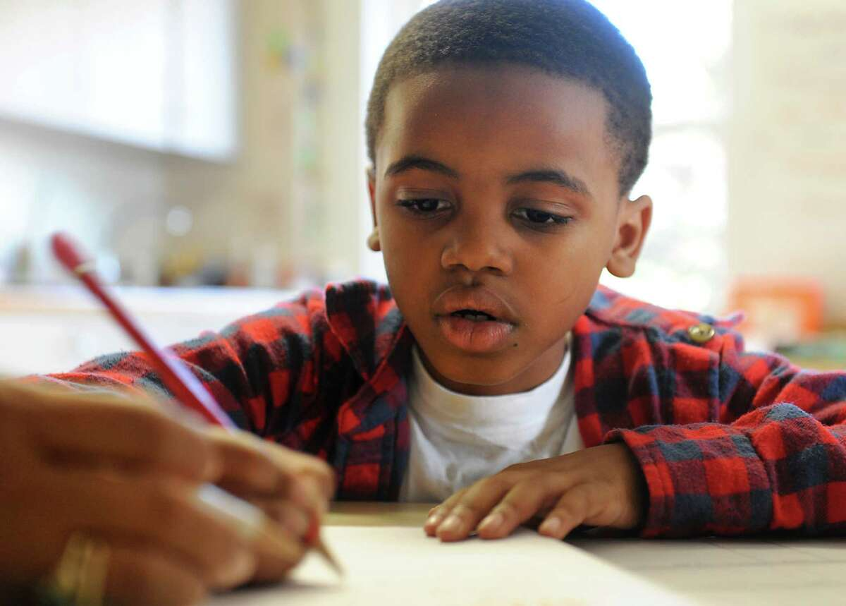 Inavion Inman, 7, of Albany practices writing at the after-school program Two Together, Inc. on Tuesday, Sept. 30, 2014 in Albany, N.Y. (Lori Van Buren / Times Union)