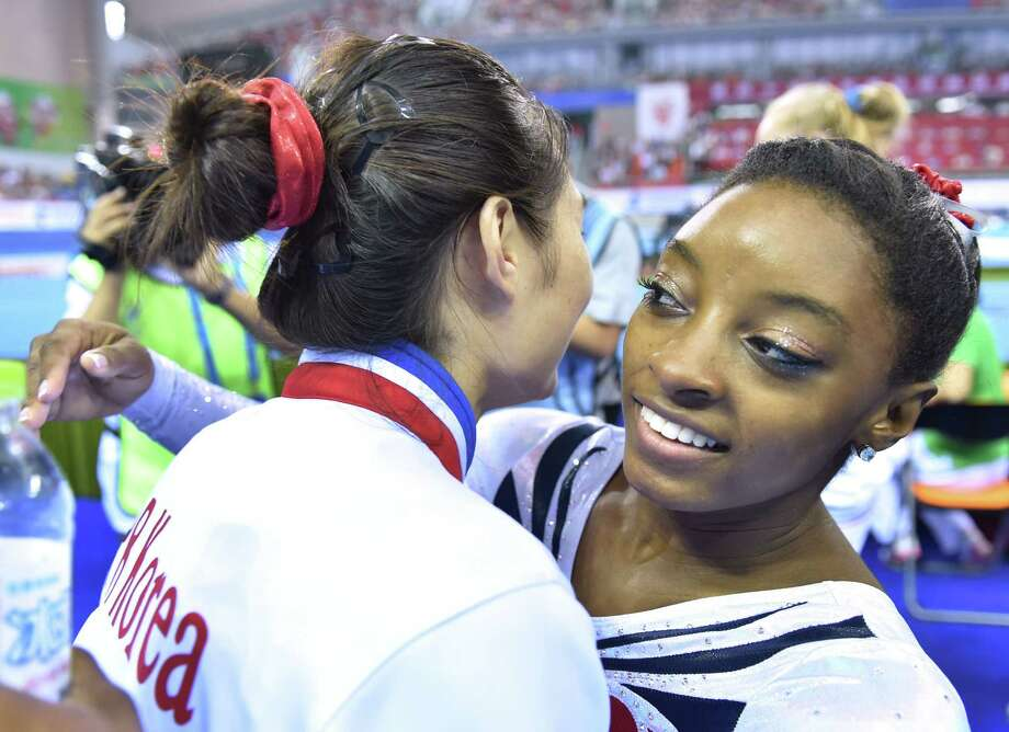 Hong Un Jong of North Korea gets a hug from Spring's Simone Biles, right, after winning the gold medal in the vault final at the gymnastics world championships Saturday in Nanning, China. Biles won the silver. Photo: KAZUHIRO NOGI, Staff / AFP