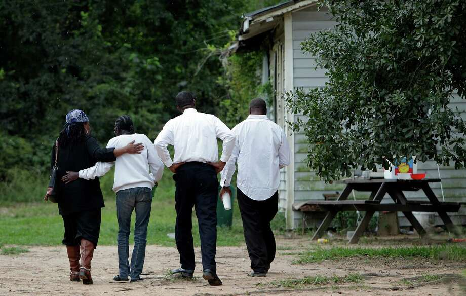 Grieving relatives of the victims walk toward their homes Saturday as the Conroe police investigated two deaths along West Santa Fe Street. Photo: Mayra Beltran, Staff / © 2014 Houston Chronicle