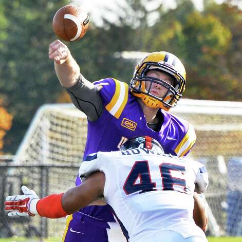 UAlbany QB Will Fiacchi gets a pass off as he's hit by Richmond's #46 Omar Howard during Saturday's game at Bob Ford Field Oct. 11, 2014, in Albany, NY.  (John Carl D'Annibale / Times Union) Photo: John Carl D'Annibale / 10028959A