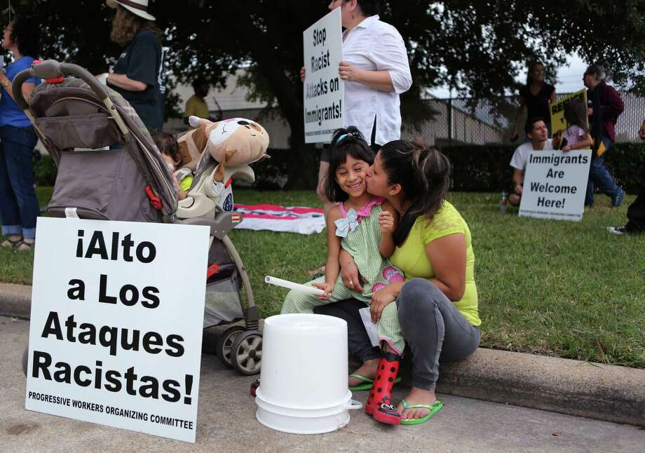 Ixtli Silva shares a moment with her aunt Zulma Vidals while drumming outside the Houston Processing Center as protestors chant, drum, and speak to oppose immigrant detention on Saturday, Oct. 11, 2014, in Houston. ( Mayra Beltran / Houston Chronicle ) Photo: Mayra Beltran, Staff / © 2014 Houston Chronicle