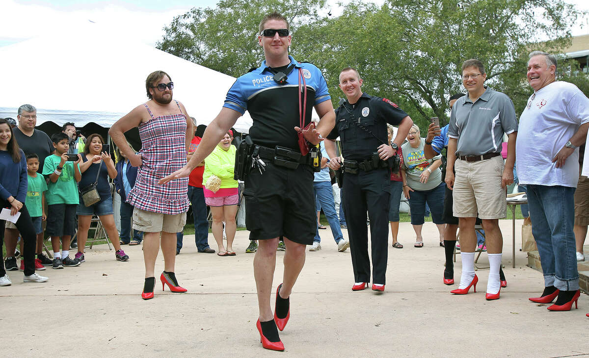 Boerne police officer Bowen Patton sashays in front of judges in high heels during the walking contest portion of the 4th Annual Walk a Mile in Her Shoes event at Main Plaza in Boerne on October 11, 2014.