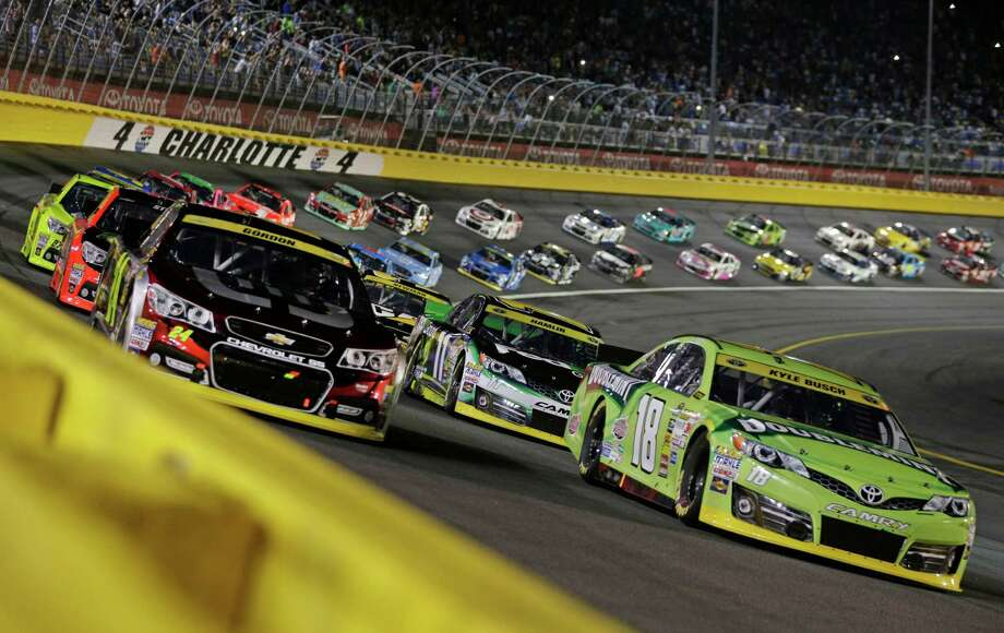 Kyle Busch (18) and Jeff Gordon (24) lead the field at the start of the NASCAR Sprint Cup series Bank of America 500 auto race at Charlotte Motor Speedway in Concord, N.C., Saturday, Oct. 11, 2014. (AP Photo/Chuck Burton) ORG XMIT: NCCB105 Photo: Chuck Burton / AP
