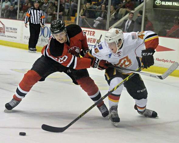 Albany Devils' #25 David Wohlberg, left, battles Adirondack Flames' #46 Bill Arnold during Saturday's game at the Glens Falls Civic Center Oct. 11, 2014, in Glens Falls, NY.  .(John Carl D'Annibale / Times Union) Photo: John Carl D'Annibale / 10028978A