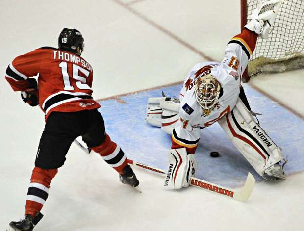 Albany Devils' # 15 Paul Thompson scores against Adirondack Flames goalie Joni Ortio in the Devil's season opener and the Flames' franchise opener Saturday Oct. 11, 2014, in Glens Falls, NY.  .(John Carl D'Annibale / Times Union) Photo: John Carl D'Annibale / 10028978A