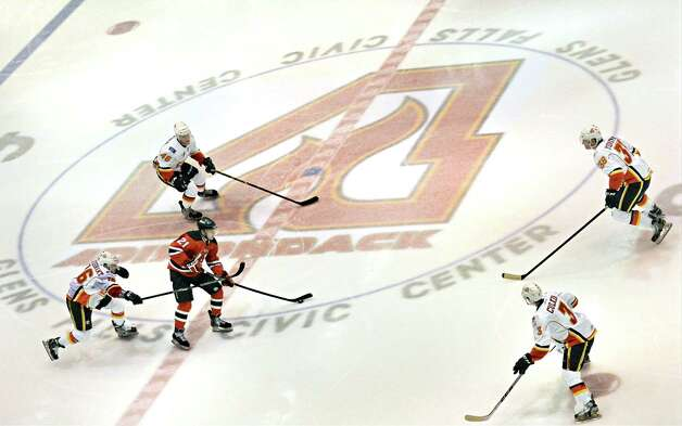 Hockey players skate over the new Adirondack Flames logo at center ice of the Glens Falls Civic Center in the Devil's season opener and the Flames' franchise opener Saturday Oct. 11, 2014, in Glens Falls, NY.  .(John Carl D'Annibale / Times Union) Photo: John Carl D'Annibale / 10028978A