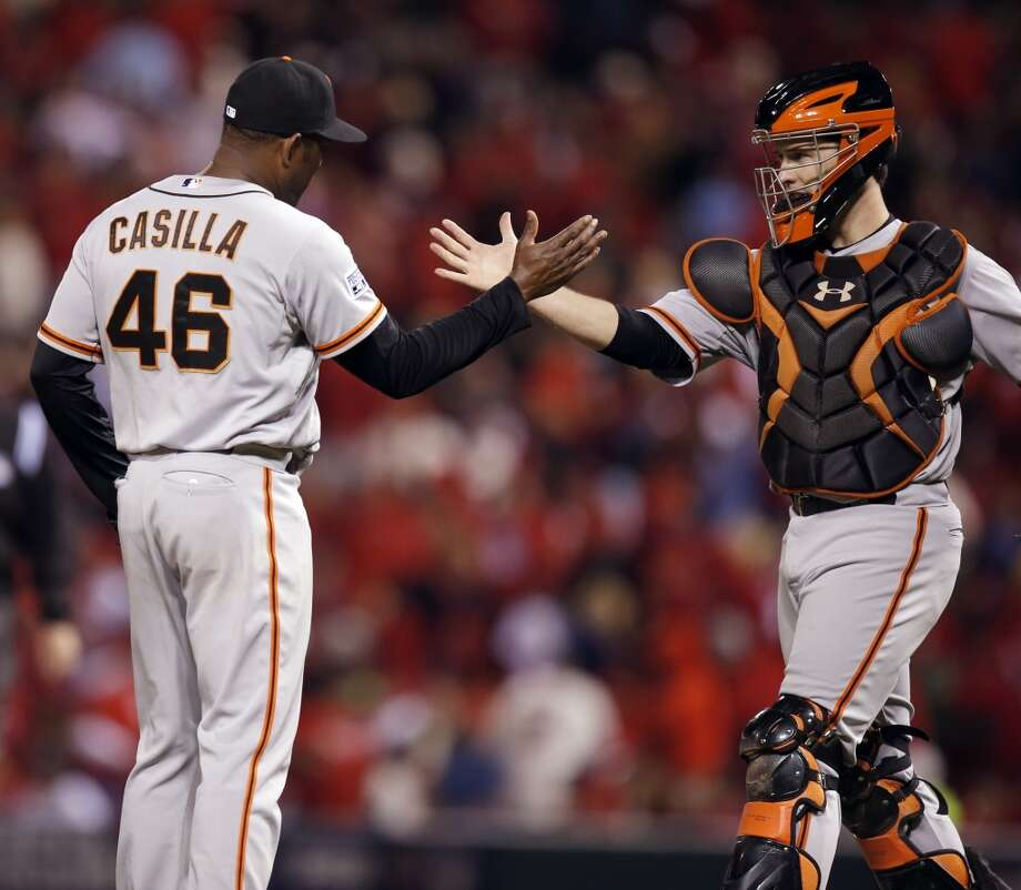 Giants Buster Posey congratulates Santiago Casilla at the end of Game 1 of the NLCS at Busch Stadium on Saturday, Oct. 11, 2014 in St. Louis, Mo.  The Giants defeated the Cardinals 3 to 0. Photo: The Chronicle