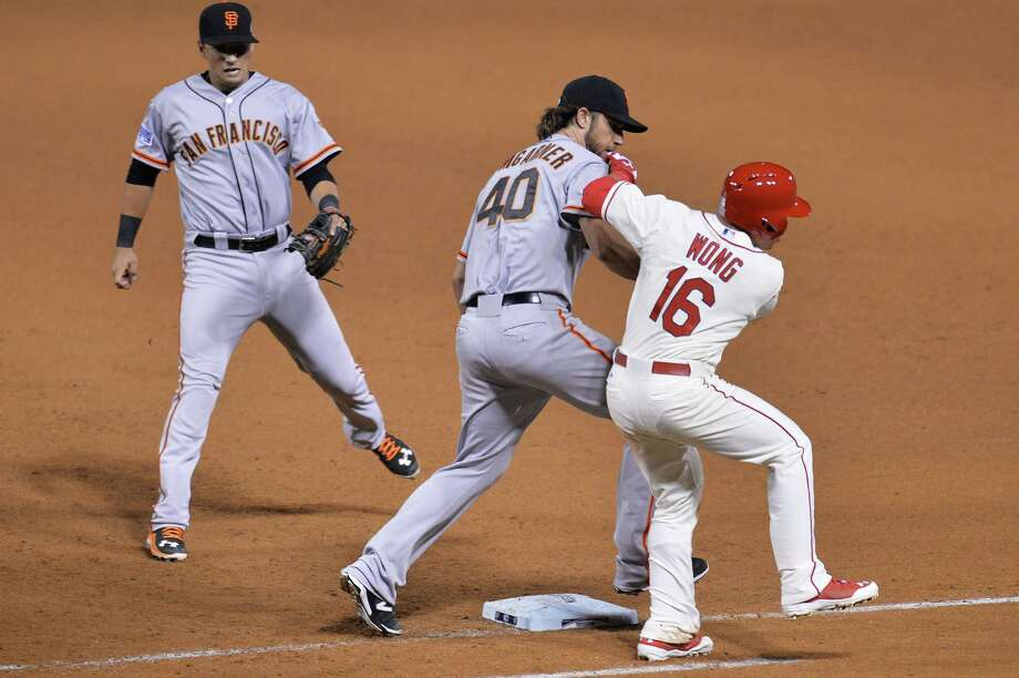 Giants starter lefthander Madison Bumgarner (40) literally kept Cardinals batters off the bases, here tagging out Kolten Wong (16) in the seventh inning. Photo: Michael Thomas, Stringer / 2014 Getty Images