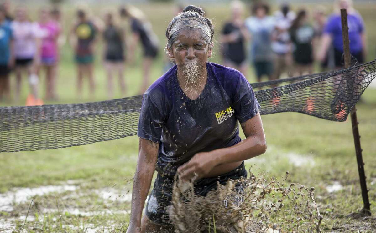 A student spits out water after clearing an obstacle during the NEISD Agriscience Magnet Program's Ag Olympics.