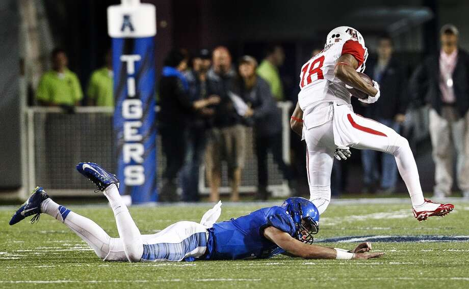 After hauling in an interception Houston's Lee Hightower (right) scrambles past diving Memphis quarterback Paxton Lynch (left) on his way to a touchdown during first half action of a college football game on Saturday, Oct. 11, 2014 in Memphis, Tenn. (AP Photo/The Commercial Appeal, Mark Weber) Photo: Mark Weber, Associated Press