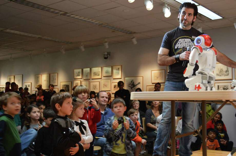 Alex Giannini, the Westport Library's manager of digital experience, had a large audience mesmerized Saturday with the library's recently acquired humanoid robots. Photo: Jarret Liotta / Westport News