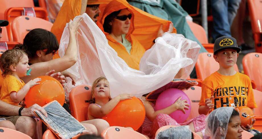 Houston Dynamo fans put on plastic covers as the rain begins to fall eventually leading to a severe weather delay during the first half of an MLS soccer match at BBVA Compass Stadium, Sunday, Oct. 12, 2014, in Houston. Photo: Karen Warren, Houston Chronicle / © 2014 Houston Chronicle