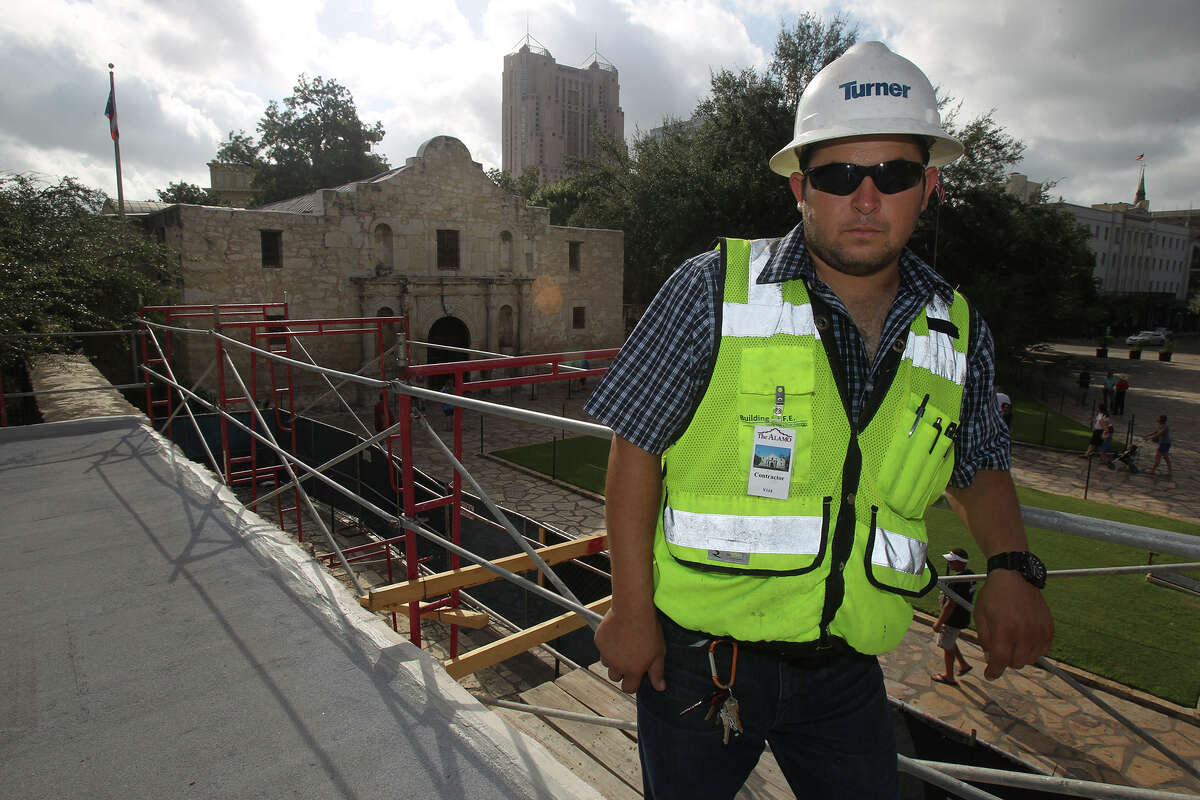 Mauricio Guzman with Turner Construction stands Friday October 11, 2014 on the new roof of the Long Barrack at the Alamo. The Long Barrack has been getting some maintenance like a new roof and a cleaning of its facade.