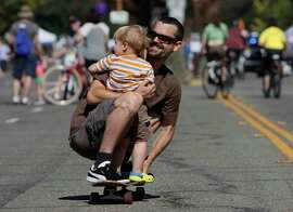 Sai Duhamel rolls down Shattuck Avenue with Donovan Fernandez, 2, during Berkeley's annual Sunday Streets. Some 50,000 people showed up for the vehicle-free party.