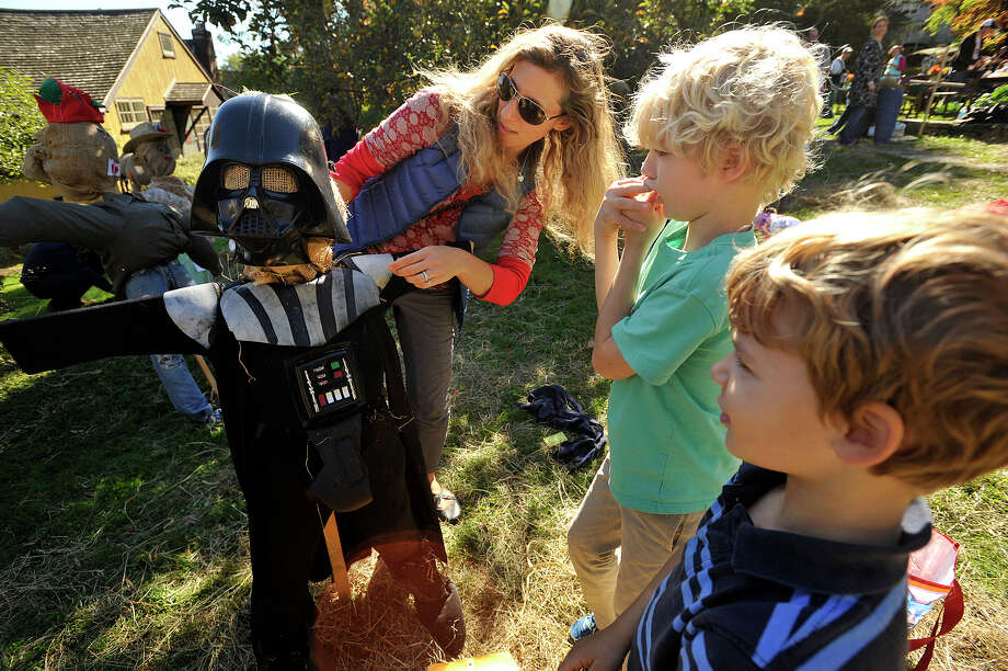 Renee Sheppard helps her children, Oliver, center, and Sebastian, put the finishing touches on their scarecrow during the Fall Festival and Scarecrow Competition at Greenwich Historical Society in Greenwich, Conn., on Sunday, Oct. 12, 2014. Photo: Jason Rearick / Stamford Advocate