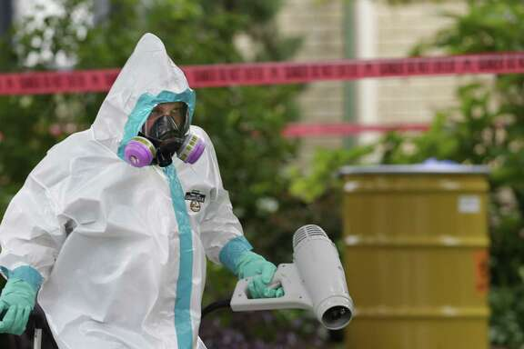 A hazmat worker clean outside the apartment building of a hospital worker, Sunday, Oct. 12, 2014, in Dallas. The Texas health care worker, who was in full protective gear when they provided hospital care for Ebola patient Thomas Eric Duncan, who later died, has tested positive for the virus and is in stable condition, health officials said Sunday. (AP Photo/LM Otero)