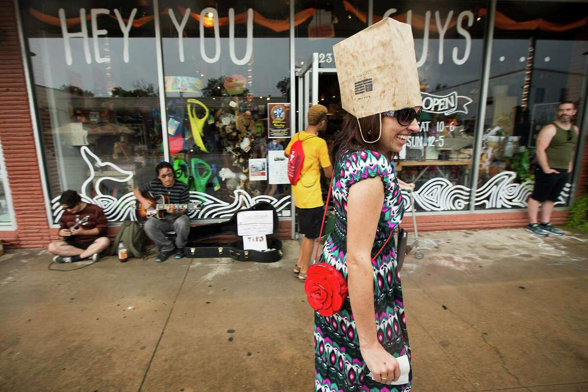 Lisa Dinga covers her head with a paper bag during a rainstorm while attending Sunday Streets HTX along 19th in the Heights on Sunday, Oct. 12, 2014, in Houston.