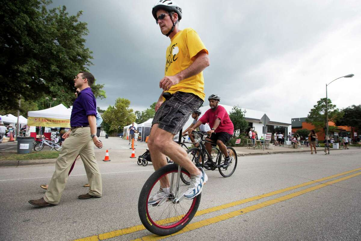John Cody rides his unicycle along 19th during Sunday Streets HTX in the Heights on Sunday, Oct. 12, 2014, in Houston.