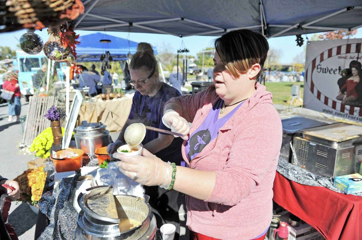 Jess Sibley, foreground, dishes out chowder as she helps her friend Susan Dunckel, owner of Sweet Sues in Troy, at the eighth annual Chowderfest at Riverfront Park on Sunday, Oct. 12, 2014, in Troy, N.Y. Dunckel's chowder was a gluten free Thai vegan tom-kha chowder. (Paul Buckowski / Times Union)