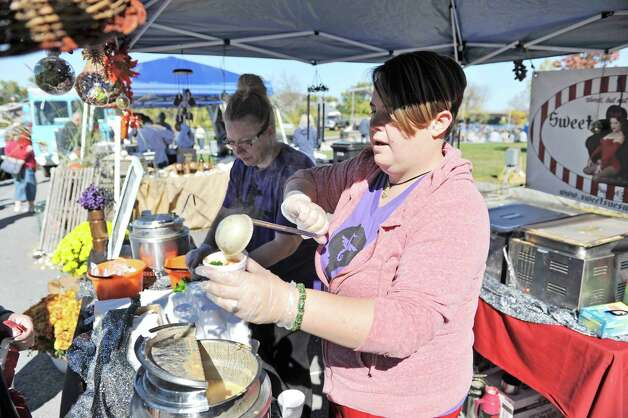 Jess Sibley, foreground, dishes out chowder as she helps her friend Susan Dunckel, owner of Sweet Sues in Troy, at the eighth annual Chowderfest at Riverfront Park on Sunday, Oct. 12, 2014, in Troy, N.Y. Dunckel's chowder was a gluten free Thai vegan tom-kha chowder.   (Paul Buckowski / Times Union) Photo: Paul Buckowski / 00028887A