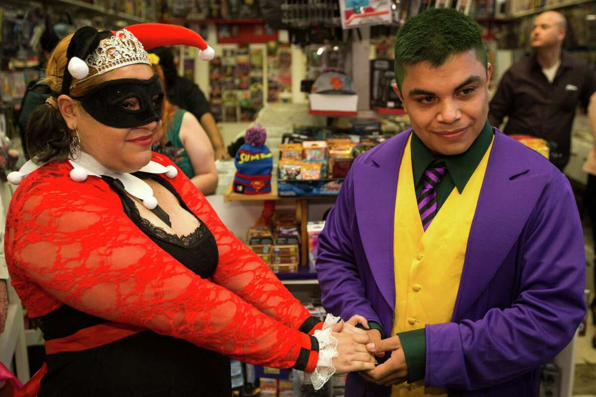 Alicia Roberson, left, and Steven Moreno exchange wedding vows during a small Batman themed wedding at Nan's Games & Comics on Sunday, Oct. 12, 2014, in Houston. The bride and groom dressed at their favorite Batman characters: Harley Quinn and The Joker.