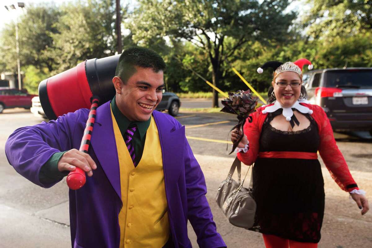 Steven Moreno, left, and Alicia Roberson arrive to their wedding for a small Batman themed wedding at Nan's Games & Comics on Sunday, Oct. 12, 2014, in Houston. The bride and groom dressed at their favorite Batman characters: Harley Quinn and The Joker.