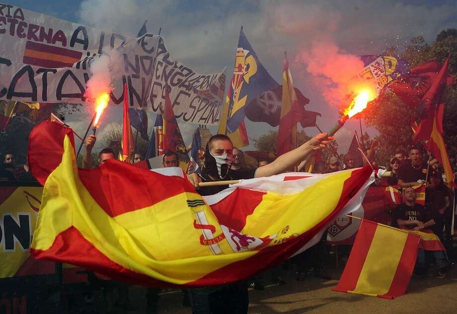 "Ultra-right wing anti-separatists burn flares during a demonstration for the unity of Spain as they celebrate a holiday known as ""Dia de la Hispanidad"" or Spain's National Day in Barcelona, Spain, Sunday, Oct. 12, 2014. Spain celebrates the day Christopher Columbus discovered America in the name of the Spanish Crown.  Photo: Manu Fernandez, Associated Press"