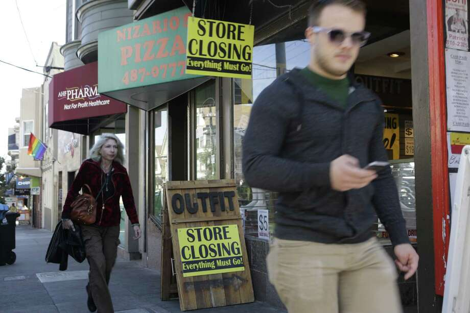 Pedestrians walk past the Outift clothing store on 18th Street in San Francisco on Friday, October 10, 2014. Outfit is moving to new, larger location, just around the corner on Castro Street. Photo: Terray Sylvester / The Chronicle / ONLINE_YES