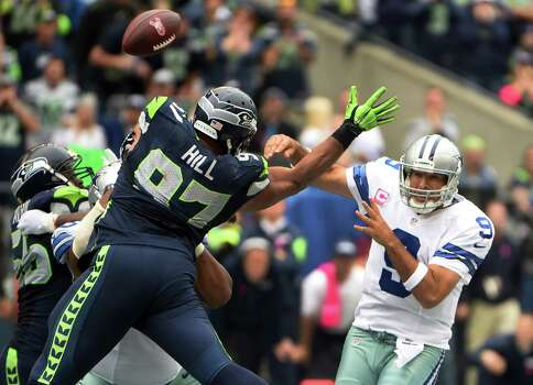 SEATTLE, WA - OCTBER 12: Quarterback Tony Romo #9 of the Dallas Cowboys passes the ball as defensive tackle Jordan Hill #97 of the Seattle Seahawks applies pressure during the third quarter of the game at CenturyLink Field on October 12, 2014 in Seattle,Washington. Photo: Steve Dykes, Getty Images / 2014 Getty Images