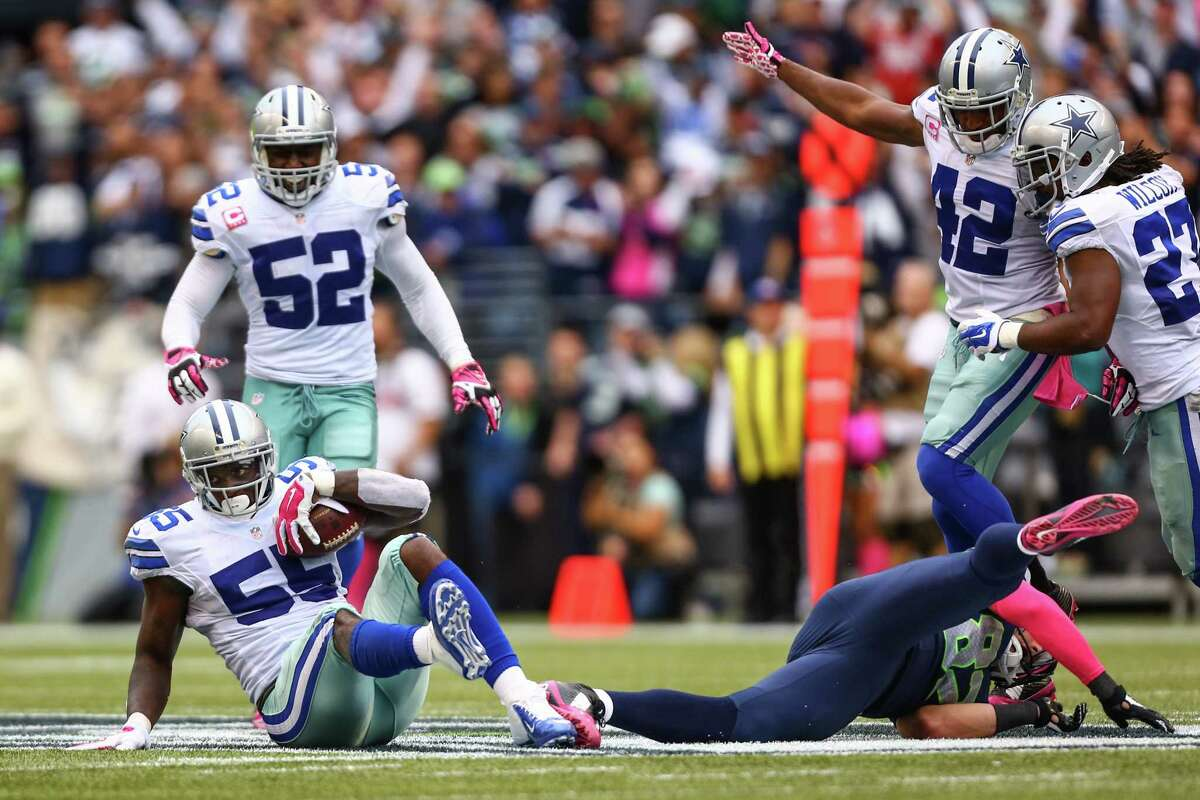Dallas Cowboys player Roland McClain (55) holds onto the ball for an interception from Luke Wilson (82) in the final seconds of a game at CenturyLink Field. The Cowboys defeated the Hawks 30-23.