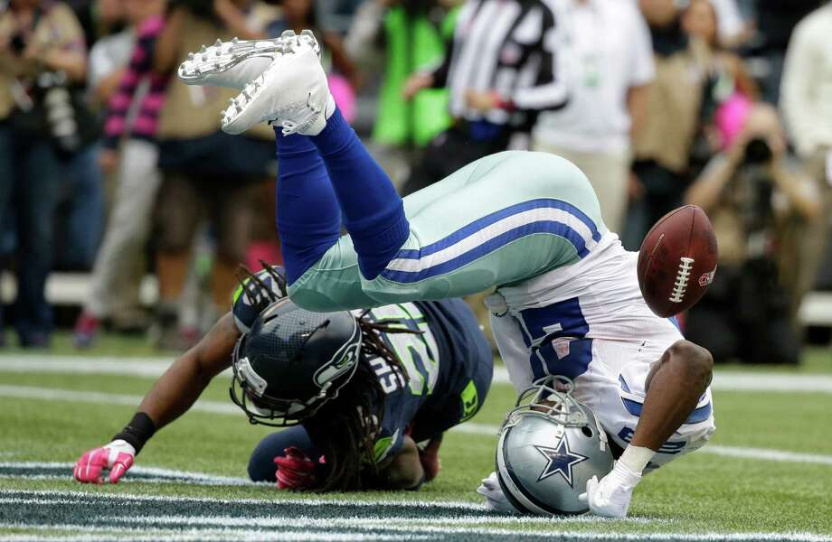 Cowboys running back DeMarco Murray takes a tumble after taking a hit from the Seahawks' Richard Sherman that couldn't prevent the go-ahead touchdown in the fourth quarter. Photo: Elaine Thompson, STF / AP