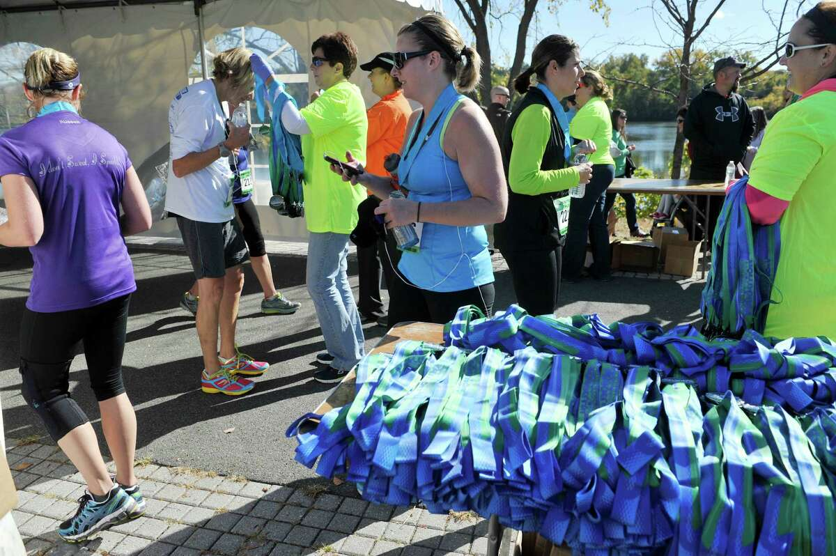 Volunteers pass out medals to runners finishing the Mohawk Hudson Marathon at Riverfront Park on Sunday, Oct. 12, 2014, in Albany, N.Y. (Paul Buckowski / Times Union)
