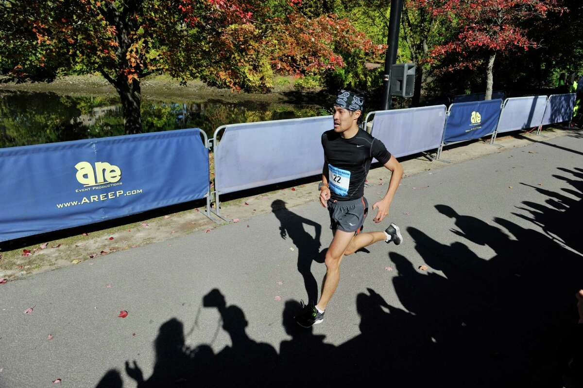 A man wearing the bib number 22, is the first runner to cross the finish line in the Mohawk Hudson Marathon at Riverfront Park on Sunday, Oct. 12, 2014, in Albany, N.Y. (Paul Buckowski / Times Union)