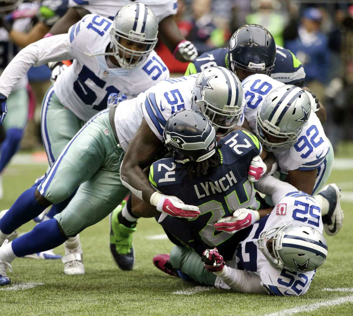 Seattle's Marshawn Lynch is bottled up by the Cowboys' Rolando McClain (55), Jeremy Mincey (92) and Justin Durant (52).