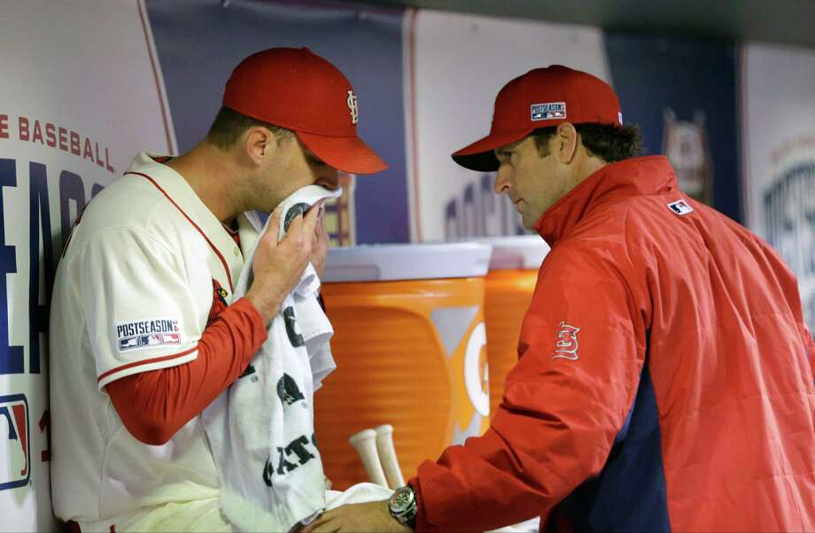 St. Louis Cardinals manager Mike Matheny, right, talks to starting pitcher Adam Wainwright after pulling him from the game during the fifth inning in Game 1 of the National League baseball championship series against the San Francisco Giants Saturday, Oct. 11, 2014, in St. Louis. (AP Photo/David J. Phillip) Photo: David J. Phillip, STF / AP