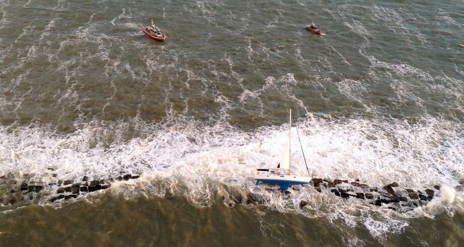 Rescuers plunked two men to safety Monday morning after their sailboat became lodged on a jetty in Galveston.  The incident began about 6 a.m. when the sailboat, French Kiss, ran aground on the tip of the south jetty, according to the Coast Guard. Swells at the time were about six feet and the wind was 30 knots. Photo: Air Station Houston, U.S. Coast Guard / Public Domain