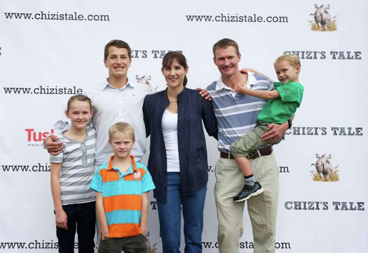 """Greenwich's Jack Jones poses with the family, the Wenham's, who inspired his book """"Chizi's Tale."""""""